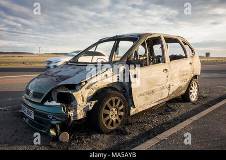 Damaged abandoned burnt out car remains at the side of the road, UK - Stock Photo