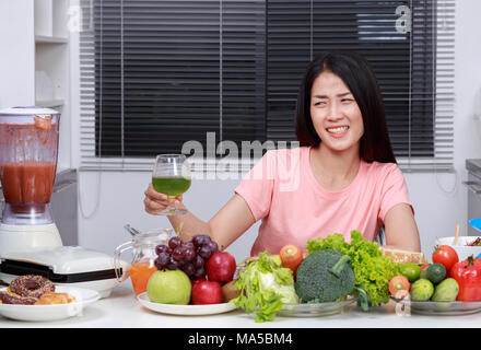 unhappy young woman drinking vegetable juice in kitchen - Stock Photo