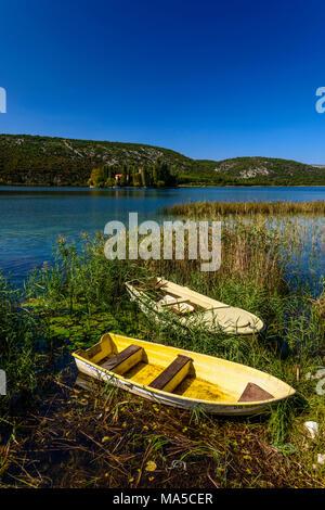 Croatia, Dalmatia, region of Sibenik, Krka National Park, Visovac Lake, Monastery Island Visovac, Visovac Monastery, boats in the foreground - Stock Photo