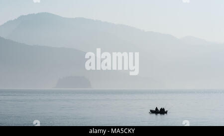 Three fishermen in a boat to the Lake Walchen / Walchensee early in the morning - Stock Photo
