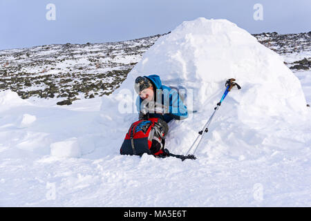 hiker pours himself a tea from a thermos, sitting in a snowy house igloo against a background of a winter mountain landscape - Stock Photo
