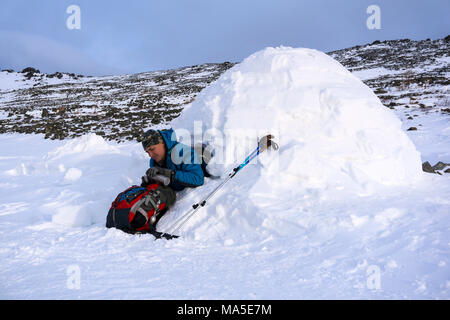 hiker pours himself a hot drink from a thermos, sitting in a snowy house igloo against a background of a winter mountain landscape - Stock Photo