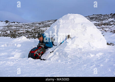 hiker pours himself a tea from a thermos, sitting in a snowy hut igloo against a background of a winter mountain landscape - Stock Photo