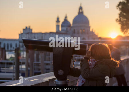 Little girl looking trough the telescope the Grand Canal, in the background the basilica di Santa Maria della Salute, Saint Mary of Health at sunset, Venice, Veneto, Italy - Stock Photo