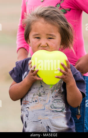 Portrait of a little boy with a yellow balloon in hands. South Gobi Province, Mongolia. - Stock Photo