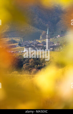 the village of Guia framed by the yellow leaves of the vineyards, as seen from the road of wine, Valdobbiadene, Treviso, Veneto, Italy - Stock Photo