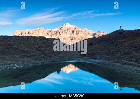 Hiker in silhouette near a small pond with Sella group with the highest Piz Boè mountain reflected, Pordoi pass, Arabba, Beuuno, Veneto, Italy - Stock Photo