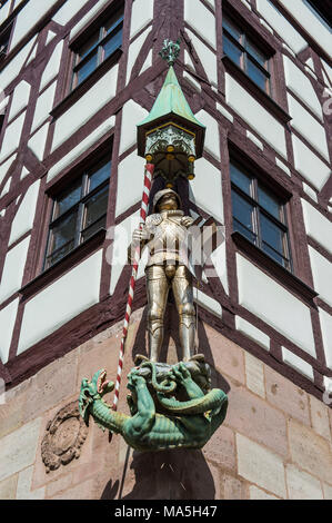 Golden statue on a half timbered house in the medieval town center of Nuremberg, Bavaria, Germany - Stock Photo