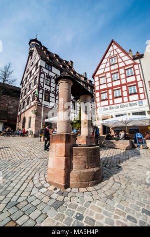 Half timbered houses and open air cafes on Albrecht Duerer square in the medieval town center of the town of Nuremberg, Bavaria, Germany - Stock Photo
