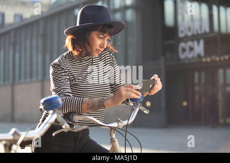Young woman by bicycle in Barcelona, Catalonia, Spain - Stock Photo