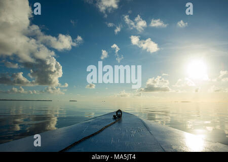 Boat detail, sun, clouds reflecting in the calm waters of Tikehau, Tuamotus, French Polynesia - Stock Photo