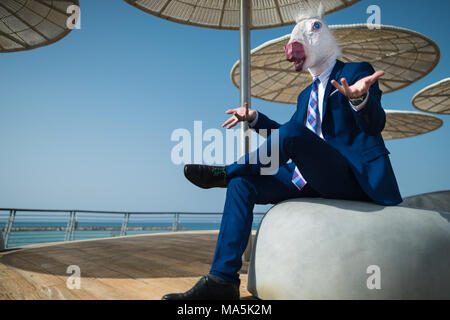 Young businessman in suit sits under umbrellas on the city waterfront and spreads hands. Unusual man in mask gesticulate on promenade. Elegant unicorn - Stock Photo