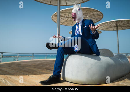 Young man in suit sits under umbrellas on city waterfront and active gesticulate. Unusual manager in comical mask spreads hands. Elegant unicorn - Stock Photo