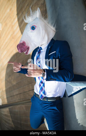 Young cool man in suit and funny mask active gesticulate. Unusual manager points to you. Unicorn spreads hands at promenade and has relax on the bench - Stock Photo