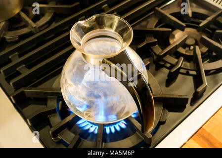 Water boiling in a One All glass Whistling Kettle by Medelco on a stovetop - Stock Photo