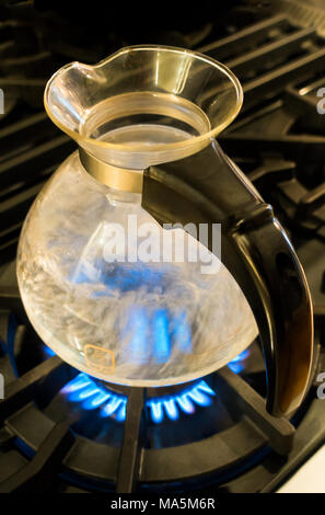 Water boiling in a One All glass Whistling Kettle by Medelco on a stove top - Stock Photo