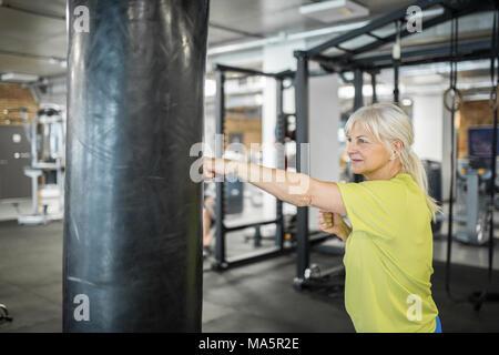 Portrait of senior woman enjoying training on punching bag - Stock Photo