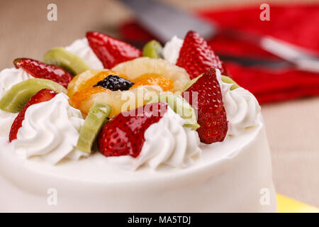 A close up of a white cake topped with various fruits. - Stock Photo