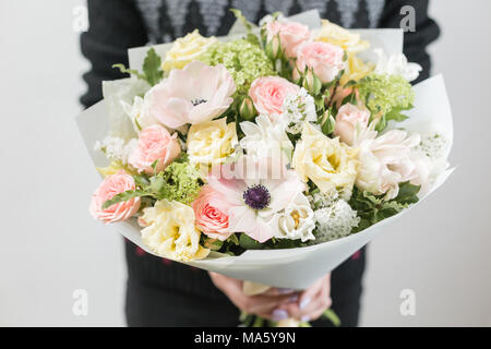 beautiful luxury bouquet of mixed flowers in woman hand. the work of the florist at a flower shop. A small family business - Stock Photo