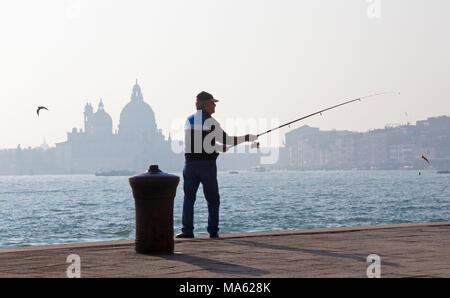 VENICE, ITALY - MARCH 14, 2014: Fisherman from Riva S. Biagio waterfront and silhouette of Santa Maria della Salute church. - Stock Photo