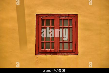 Antique red wooden window isolated against a vintage yellow wall of a traditional Singapore shophouse in historic Chinatown with space for copy - Stock Photo