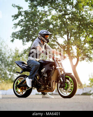 Ivano-Frankivsk, Ukraine - 28 August 2015 : Young biker ,wearing protective colorful helmet is posing sitting on sport motorcycle on sunny city street. Green plants and trees on background. - Stock Photo