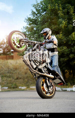 Ivano-Frankivsk, Ukraine - 28 August 2015 : Confident biker performing extreme stunts on sport motorcycle . Man stands on one backwheel of bike on the road near green trees on background.. - Stock Photo