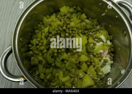 Pasta with green vegetables and creamy sauce in copper saucepan. Grey stone background - Stock Photo
