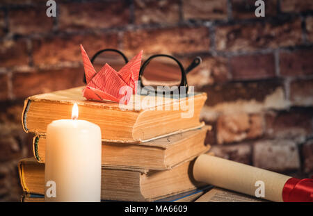 Pile of books with origami on the top, candle, book, notebook,pencil and glasses on the wood brown background against old brick wall - Stock Photo