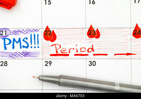 Reminder PMS and Period in calendar with red pen. Closeup. - Stock Photo
