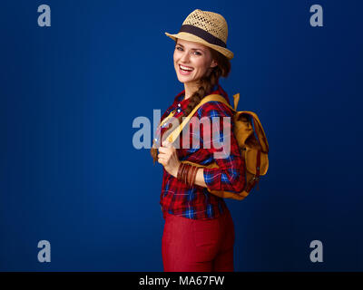 Searching for inspiring places. Portrait of happy active tourist woman with backpack isolated on blue background - Stock Photo