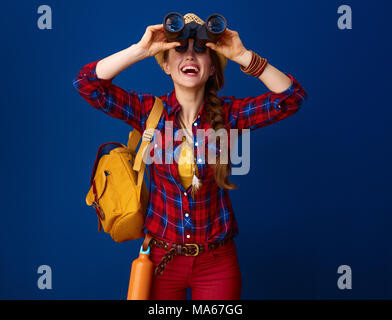 Searching for inspiring places. happy fit tourist woman with backpack looking up through binoculars on blue background - Stock Photo