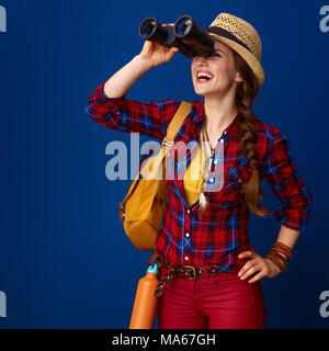Searching for inspiring places. happy active woman hiker with backpack looking into the distance through binoculars against blue background - Stock Photo