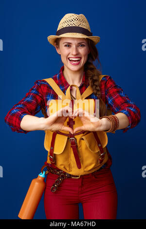Searching for inspiring places. smiling young traveller woman with backpack showing heart shaped hands isolated on blue - Stock Photo