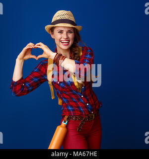 Searching for inspiring places. happy active tourist woman in a plaid shirt showing heart shaped hands against blue background - Stock Photo