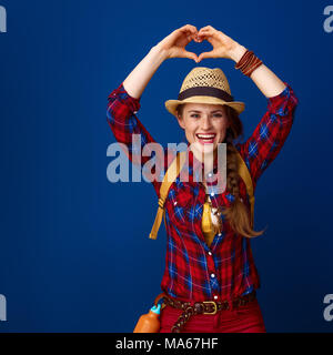 Searching for inspiring places. happy healthy traveller woman in a plaid shirt showing heart shaped hands isolated on blue - Stock Photo