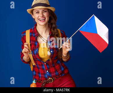 Searching for inspiring places. happy active traveller woman with backpack showing the flag of Czech isolated on blue background - Stock Photo