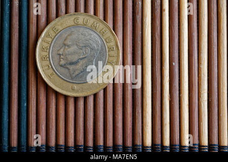 One Turkish coin denomination is 1 lira lie on wooden bamboo table, good for background or postcard - back side - Stock Photo