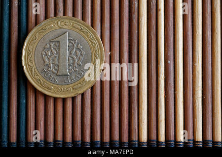 One Turkish coin denomination is 1 lira lie on wooden bamboo table, good for background or postcard - Stock Photo