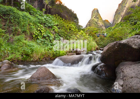 Tourists crossing bridge under the Maui Iao Needle with Iao Stream in the foreground at Iao Valley State Park, Maui, Hawaii. - Stock Photo