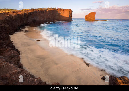 """Sunset light on the clouds above Puu Pehe Rock, also known as """"Sweetheart Rock"""", one of Lanai's most recognizable landmarks, Lanai Island, Hawaii, USA - Stock Photo"""