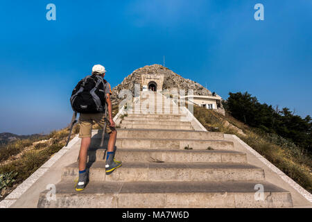 Njegusi mausoleum in Lovcen National Park - Young tourist boy  with backpack climbing the steep stairs to the entrance - Stock Photo
