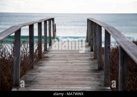 Wooden walkway to the beach and waves. - Stock Photo