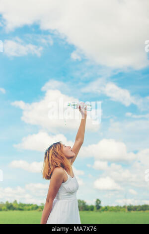 young woman in park pours water over a face for freshing at grassland enjoy and happy life