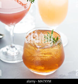 Variety of citrus cocktails with ice and herbs on gray surface - Stock Photo