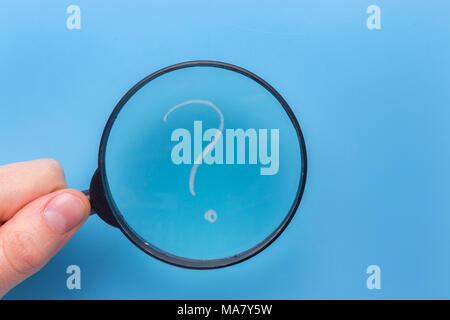 question mark under a magnifying glass with blue background - Stock Photo