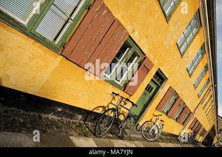 Bicycles against yellow house in Nyboder, Copenhagen, Denmark - Stock Photo