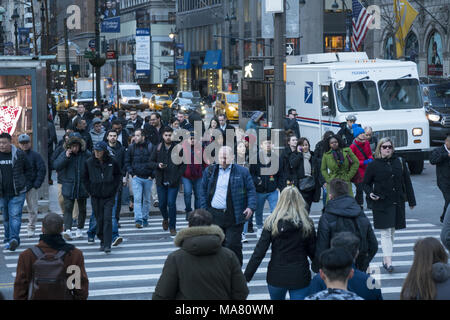 Pedestrians in the crosswalk at the always busy corner of 5th Avenue and 42nd Street in midtown Manhattan, NYC. - Stock Photo