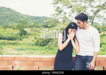 portrait of man hugging upset woman on black Stock Photo ...