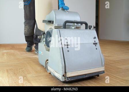 Sanding hardwood floor with the grinding machine. Repair in the apartment. Carpenter doing parquet wood floor polishing maintenance work - Stock Photo